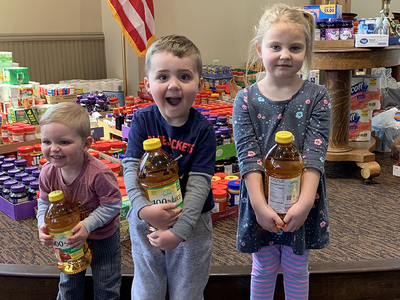 three young children hold bottles of apple juice. A bunch of donated canned goods and food are behind them.